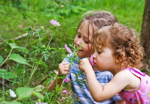 Little girls smelling flowers
