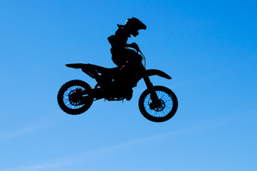 motocross rider making a high jump against a blue sky