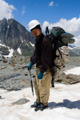 Climber in crampon and helmet standing on snow in mountains