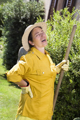 Tired senior Italian woman having backache while gardening
