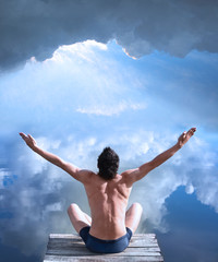 A man is sitting with his hands raised in the air