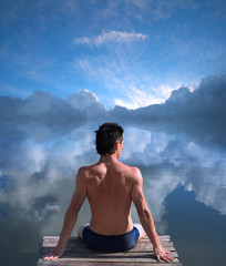 A man is sitting at the water where the blue sky is mirrored