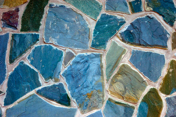 colored (prevaling blue) rough wall surface made of wild stones