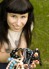 closeup portrait on young brunette holding a lot of beads