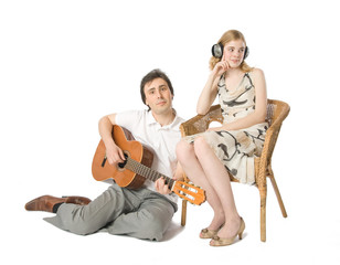 A woman in headphones and a man playing guitar for her