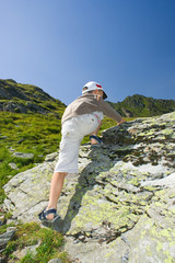 Young boy climbing up on a mountain