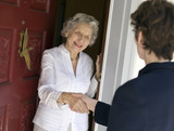 Smiling senior woman greeting visitor at the front door poster