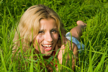 Beautiful girl lays on a green grass