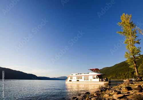 A luxury house boat beached on a beautiful lake