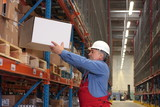 senior worker in uniform putting box on shelf in warehouse poster