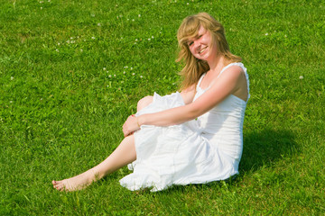 Girl in a white dress sits on a green grass