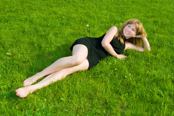 Girl in a black dress lays on a green grass