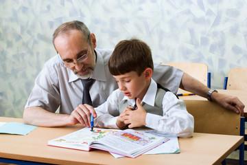 Teacher and schoolboy read alphabet. Primary school.