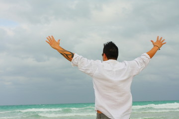 Man facing the ocean with arms extended