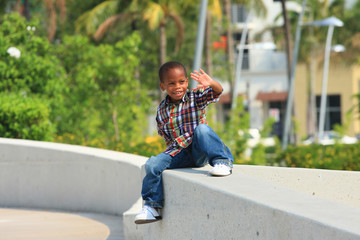 Boy waving from a ledge