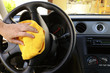 Woman's hand with microfiber cloth polishing steering wheel
