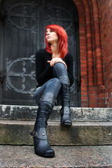 girl with red hair is sitting on the stairs