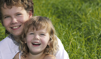 two children portret smiling on green grass