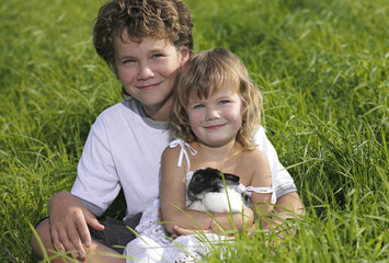 two children smiling sitting on green grass with rabbit