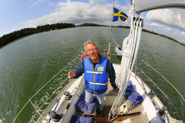 Happy sailor navigating his boat in the archipelago