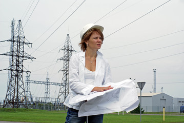 Woman engineer with safety hat drawings and electrical towers