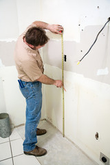 Construction worker measuring wall during kitchen remodel