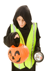 Adorable little boy on halloween with a reflective vest & torch
