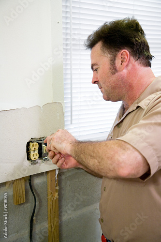 Electrician replacing old receptacle during kitchen remodel