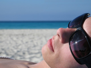 girl with sunglasses tanning on the beach