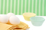 three eggs on napkin with cupcake baking paper cups poster