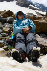 Girl in crampon relaxing on snow in mountains