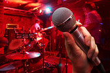 hand with microphone on a nightclub background poster