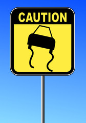 black and yellow caution sign against blue sky - road slippery