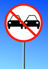 no passing road sign with two cars against a blue sky