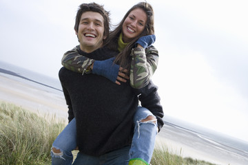 Portrait of happy young couple at beach