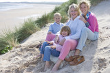 Multi-generation family sitting on beach