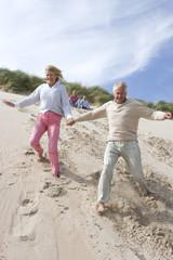 Senior couple running down on beach