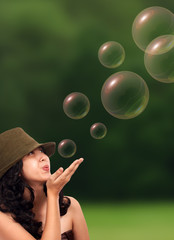 gorgeous young girl with soap bubbles outdoor