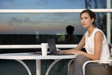 Businesswoman using laptop at outdoor cafe