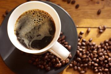 schwarzer kaffee mit schaum und kaffeebohnen
