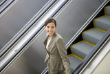 Businesswoman riding on escalator