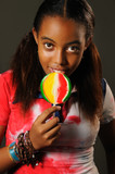 young african girl eating a lollipop with happy expression poster
