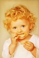 A little girl eating a biscuit