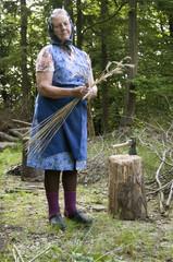 Alte Bauernfrau bindet Stroh bei Waldarbeit