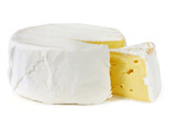 A wheel of rich creamy brie cheese, with a wedge cut out.