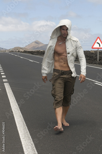 muscled man walking on the road without shoes
