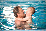 Grandfather and grandson swimming together in the pool. poster