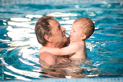 Grandfather and grandson swimming together in the pool.