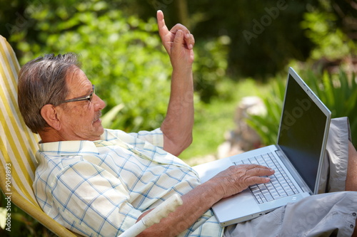 Healthy senior man in his elderly 70s using laptop computer