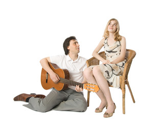 A blond girl and a man playing guitar for her
